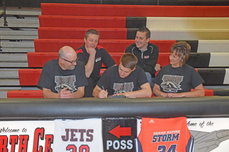 Mike Mattson | Daily Press North Central senior Jason Whitens signed his national-letter-of-intent Friday to attend Western Michigan University and play basketball. Joining Whitens for the signing in the front row were his parents Gerald and Faye Whitens. In back row from left are:  Varsity basketball coach Adam Mercier and Athletic Director Joey  Pontbriand.