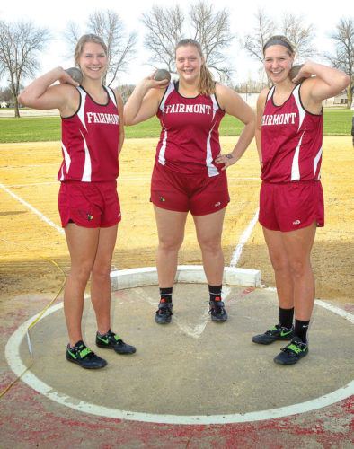 A-B-C — Fairmont Cardinals throwers, from left, Brenna Cutler, Alli Lardy and Claire Cutler hoist their respective shots prior to Tuesday's outdoor season-opening track &field in Fairmont. The talented throwing trio has literally made their marks in the Cardinals' track & field record books this season. (Photo by Greg Abel)