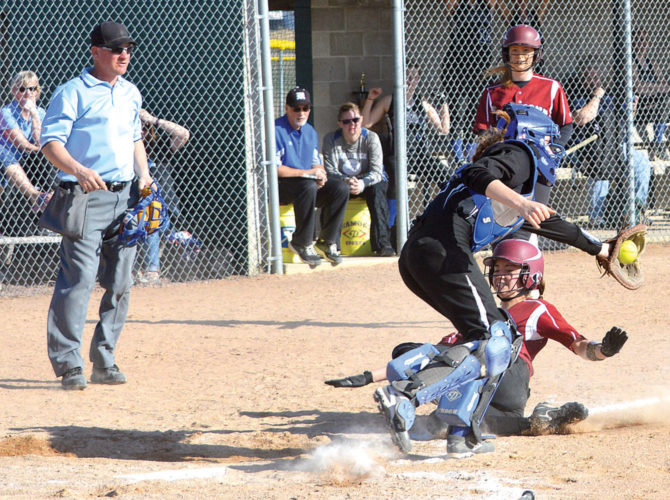 SAFE AT HOME — Fairmont Cardinals runner Ericka Kim slides safely past Martin County West catcher Karlee Thiesse as Thiesse fields the throw to the plate during the championship game of the Martin County West softball invitational on Saturday at Fox Lake Sports Complex in Welcome. Fairmont's Jordan Ehlert (back right), Martin County West coaches Darrell Ziegler and Jen Clow (back center), and home plate umpire Joel Erdman watch the action. (Photo by Charlie Sorrells)