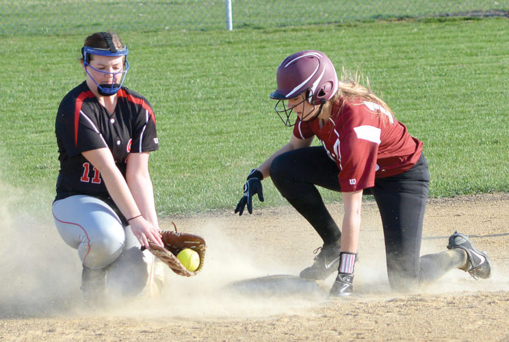 STIRRING UP THE DUST — Fairmont runner Taylor Crissinger (right) beats the low throw to Worthington second baseman Brittin Fauskee for a stolen base during Big South Conference softball action Tuesday at Cardinal Park in Fairmont. (Photo by Charlie Sorrells)