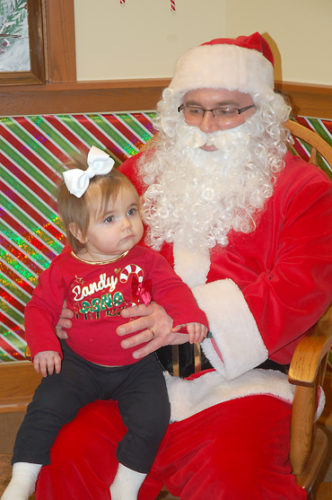 —Daily Freeman-Journal file photo Little Cora Graser sits on Santa's lap while her parents snap photos. Santa made an appearance last year at Kendall Young Library during the Santa's Workshop event.