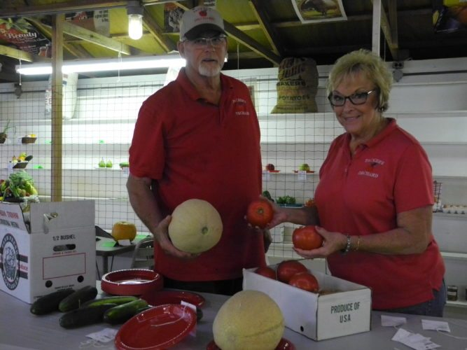 WINNERS — Bill and Marty Packer of Packers Orchard on state Route 250, Harrisvile, set out produce that was judged at the Jefferson County Fair. Their apples and peaches came in first in the competition. -- Esther McCoy
