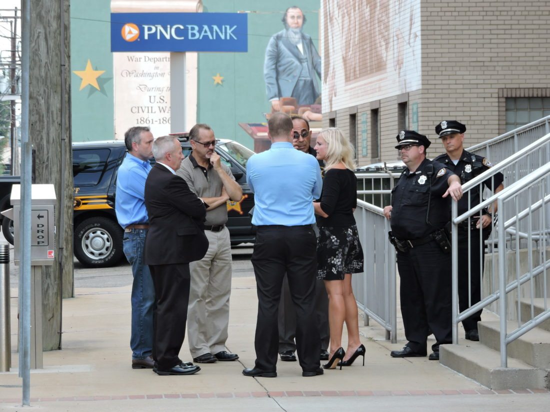 A SOMBER SIDEWALK CONFERENCE — Jefferson County commissioners, from left, Thomas Graham, David Maple and Tom Gentile listened while assistant Prosecutor Jeff Bruzzese, Sheriff Fred Abdalla and Prosecutor Jane Hanlin discussed the apparent suicide of convicted felon Jason Binkiewicz Friday morning in the Jefferson County Courthouse. Standing guard at the side entrance to the courthouse were City Police patrolmen Shawn Scott and Eric Hart. — Dave Gossett