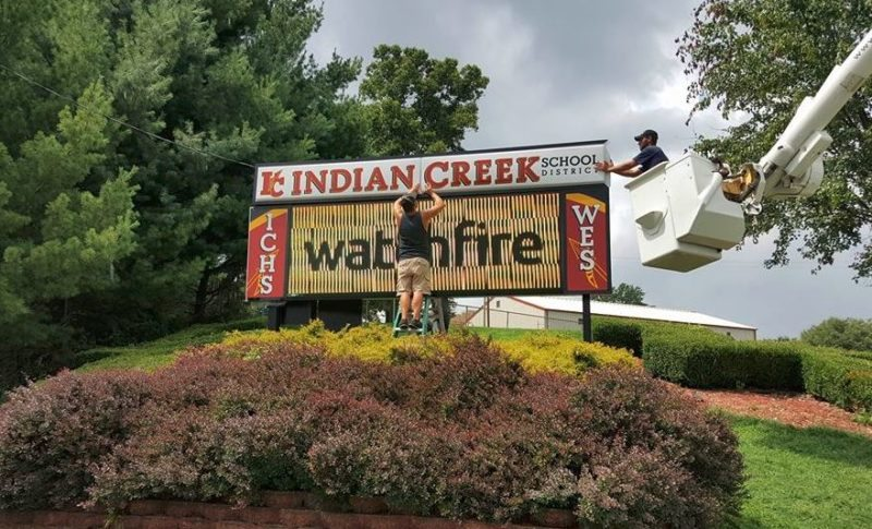 Workers install the new sign near the entrance of Indian Creek High School and Wintersville Elementary School., — Contributed
