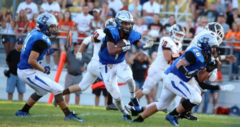 FINDING DAYLIGHT — Harrison Central's DeJuan Caldwell runs with the ball between teammates Tucker Coultrap (24) and Coleman Dodds during Friday's season-opening win over Claymont, 52-41. (Sandi Thompson)