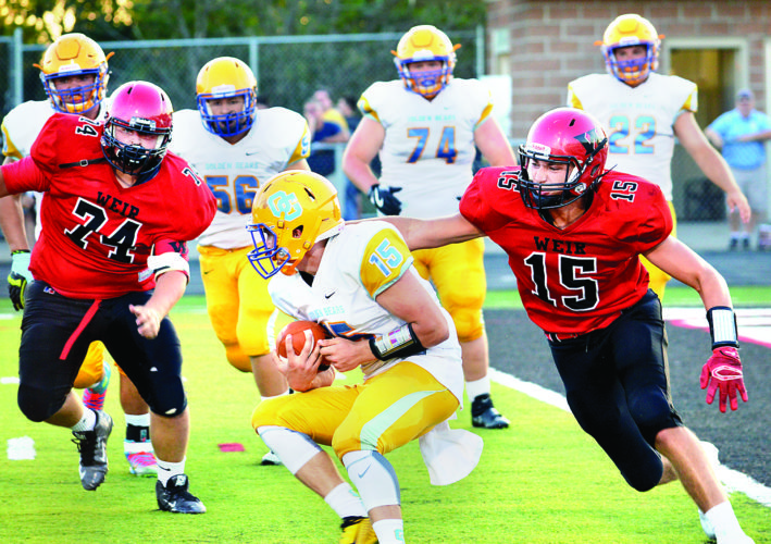 SURROUNDED ON OPENING NIGHT — Weir High's Tyler Komorowski (15) and Garrett Johnson surround Oak Glen quarterback Lance Collins during the first half of Friday's Battle of Hancock County at Jimmy Carey Stadium. The Red Riders won the Carl Hamill Trophy with a 41-0 victory over the Golden Bears. Weir welcomes Edison next week, while Oak Glen hosts Steubenville Catholic Central. (Michael D. McElwain).