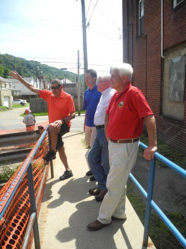 City officials took state officials on a tour of Follansbee to assess flood damage and recovery Saturday. Those involved in the tour were, from left, City Manager John DeStefano; Mayor Dave Velegol Jr.; Mark Fitzsimmons, conservation district supervisor for Marshall County; and Walt Helmick, West Virginia agriculture commissioner. — Mark J. Miller