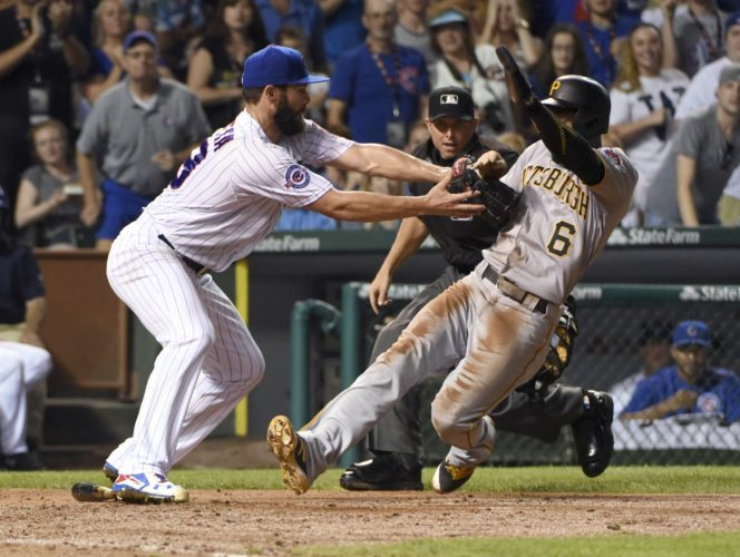 Chicago Cubs starting pitcher Jake Arrieta (49) tags out Pittsburgh Pirates' Starling Marte (6) at home plate during the fifth inning of a baseball game, Monday, Aug. 29, 2016, in Chicago. (AP Photo/David Banks)