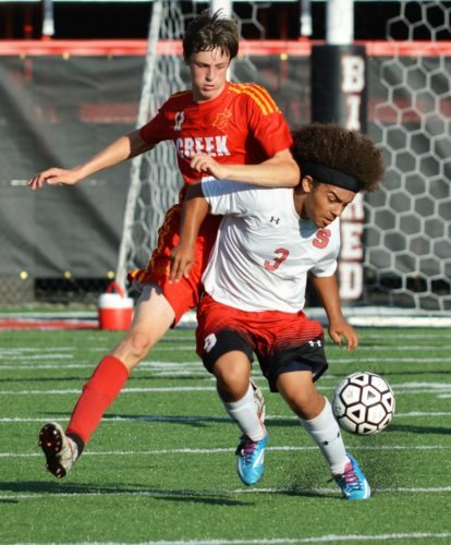 PLAYING IT TIGHT — Steubenville's Marc Porter and Indian Creek's Nathan Jones battle for the ball in the first half of Tuesday's 6-0 Big Red win inside Harding Stadium. (Mike Mathison)