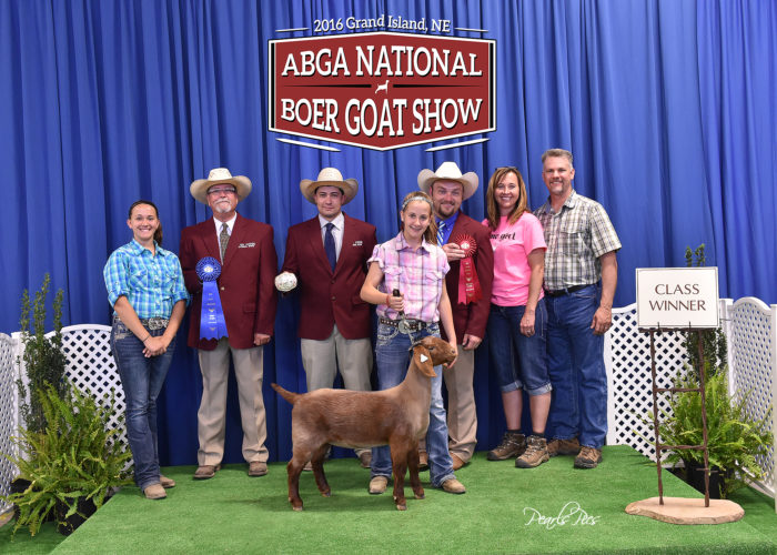 ENJOYING NEW VENTURE  — Raising and showing Boer goats is a relatively new venture for area residents Tom Valuska, back right, and his wife, Kelly, next to him, of Hard Rock Farm Boer Goats and their daughters, Megan, left, and Emily, front, shown at the June American Boer Goat Association National Boer Goat Show held in Grand Island, Neb., and involving 36 states competing. Honors there included second in the massive 3-6 month Open Full Blood Class, second in 3-6 month Junior Full Blood Class and first in Breed and Owned.  -- Contributed