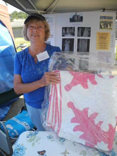 FESTIVAL CONTINUES — Vivian Weigel, vice president of the Hancock County Museum, shows off an antique quilt to be drawn off during the annual New Cumberland Fall Riverfest Saturday. The festival continues 11 a.m. to 5 p.m. today.