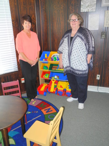 NON-THREATENING ENVIRONMENT — Eileen Spencer, left, child and family advocate for A Caring Place Child Advocacy Center, and MaryAnn Donnelly, the center's director, are seen in among the children's furniture and toys intended to help children feel more comfortable while being interviewed about possible cases of child abuse and other issues. - Warren Scott