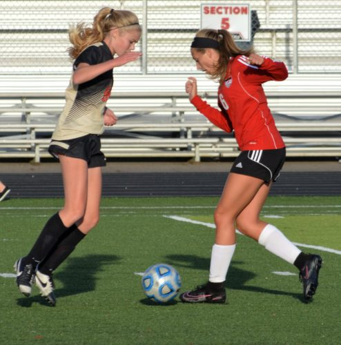 IN THE MIDDLE — Weir High's Taylor Quickle, right, and University's Rachel Gaspar battle for the ball in Tuesday's game. The visiting Hawks beat the Red Riders, 4-1. (Mike Mathison)