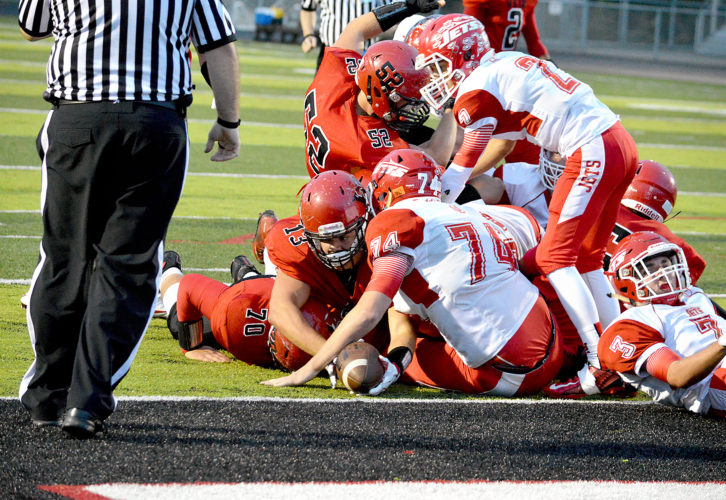 AT THE GOAL LINE — Weir High's Cody Enrietti reaches to the goal line as his Red Riders teammates Travis Lowther (52) and Zach Martin lay down blocks. Weir beat Union Local, 42-14, on Homecoming. (Michael D. McElwain)