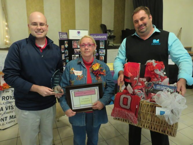 Cherry Bennett was named Caregiver of the Year and is shown with plaque presenter Matt Wight, left, one of the many exhibitors on hand, and Chris Orris, physician liaison, Valley Hospice, which donated a basket of items for the honoree.  -- Janice Kiaski