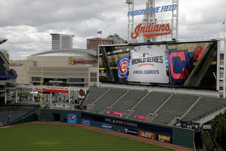Progressive Field, home of the Cleveland Indians, is setup for baseball's upcoming World Series against the Chicago Cubs and the Quicken Loans Arena is seen in the background on Monday, Oct. 24, 2016 in Cleveland. On Tuesday, Cleveland will be on center stage of the sports universe and will have a downtown celebration beyond anything that has happened here before. The Cavaliers' banner is raised in Quicken Loans Arena before their season opener and at Progressive Field, the Indians will host the Chicago Cubs in Game 1 of the World Series. (AP Photo/Charlie Riede)