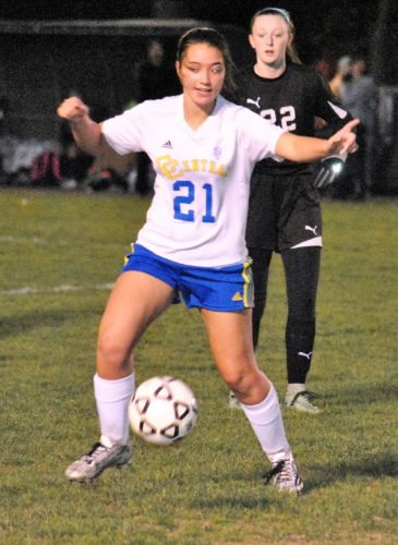 Matthew Peaslee UNDER THE LIGHTS — Catholic Central's Rachel Ledyard balances the ball in the first half in front of Edison's Lauren Ferralli Wednesday.