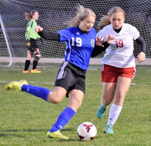 Kim North MAKING A PLAY — Harrison Central's Sydney Starr and Zanesville Bishop Rosecran's Ryin Browning battle for possession of the ball during Wednesday night's Division III Eastern District tournament semifinal game at the Southeastern Community Park in New Philadelphia.