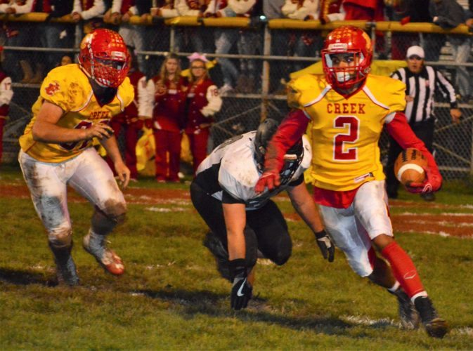 MAKING A MOVE — Indian Creek quarterback Greg Wade escapes Edison's Mason Balzano during Thursday's contest at Kettlewell Stadium. The Redskins finished the season at 8-2 with a 35-13 victory in the Route 43 Rivalry. Looking on is Creek's Andy Waggoner. (Mike Mathison)