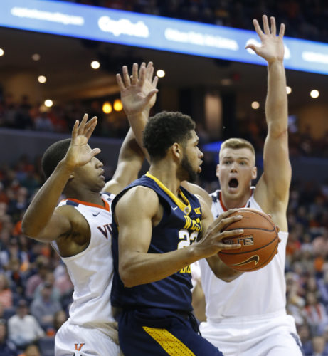 West Virginia forward Esa Ahmad (23) is pressured by Virginia center Jack Salt, right, and Virginia guard Devon Hall, left, during the first half of an NCAA college basketball game in Charlottesville, Va., Saturday, Dec. 3, 2016. (AP Photo/Steve Helber)