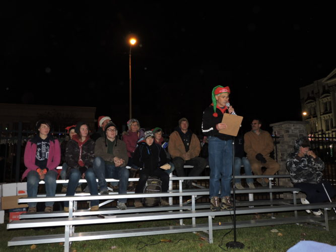 Members of the Nelson family sat on the bleachers during the Steubenville Lights Up the Night event last month in the Fort Steuben Park listening to Jerry Barilla of the Historic Fort Steuben praise the family for creating the Nutcracker Village and Advent Market. The Nelson family will serve as the grand marshals for Saturday's 2016 Sights and Sounds of Christmas Parade in downtown Steubenville. — Dave Gossett