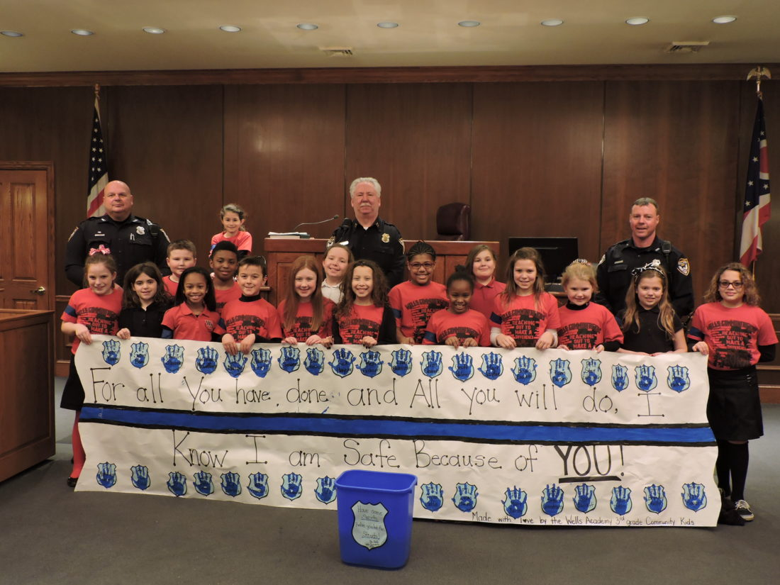 The Wells Academy Community Kids third-graders presented sweets and a hand painted banner to the Steubenville Police Department Monday afternoon as part of Law Enforcement Appreciation Day. The third-graders, under the guidance of Wells Academy teacher Julie Battistel, met with, from left, Patrolman Jim Marquis, Capt. John Young and Patrolman Shawn Extrovich in the Municipal Courtroom. The children had an opportunity to ask the police officers and Municipal Court Judge John Mascio questions about their jobs. - Contributed