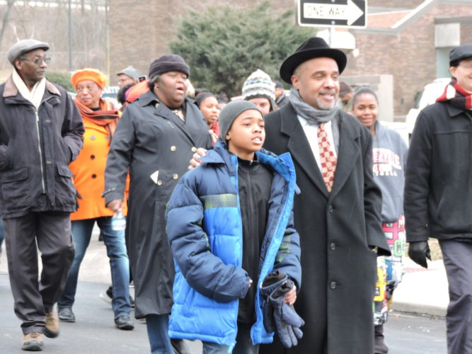 MARCHINGINMEMORYOFKINGJR. — The Rev. Vaughn Foster marched on the streets of downtown Steubenville Monday with his 12-year-old son Elijah during the annual Dr. Martin Luther King Jr. commemorative march. The march began at the MLK Recreation Center and ended at Steubenville High School. - Dave Gossett