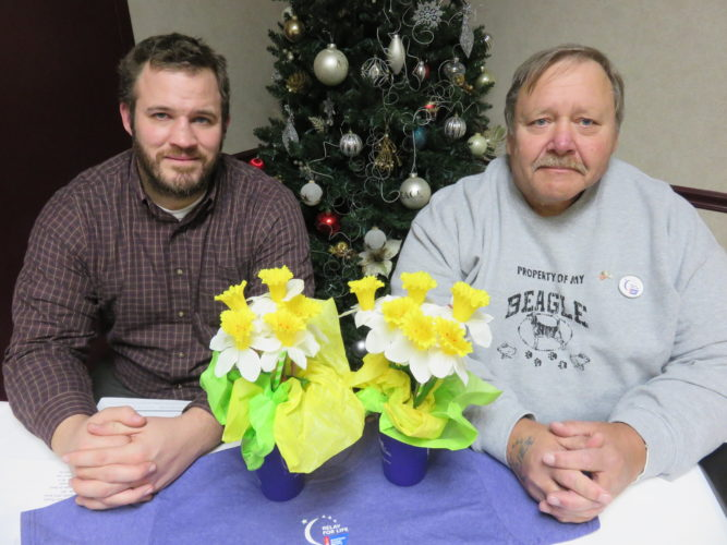 FLOWER OF HOPE — Eric Baker, left, American Cancer Society community manager, and Dan Wood, chair of the 22nd-annual Steubenville Area Relay for Life to benefit the ACS, explained to participants at the January planning meeting that daffodil sales have returned as a fundraiser. Order are being accepted through Feb. 15 for daffodils two ways — a bunch of 10 daffodils for $10 or a potted plant of six daffodils for $12. Orders can be placed through any teams or Baker by phone at (888) 227-6446, extension 2226 or by e-mail at Eric.Baker@cancer.org or Wood at (740) 317-6101. -- Janice Kiaski