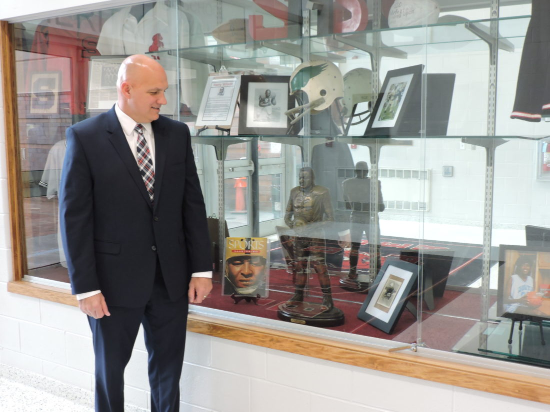 ONE OF THE BEST — Steubenville High School Principal Ted Gorman stands next to a display case containing a smaller version of the Calvin Jones statue that will be placed at the main entrance of Harding Stadium later this year. - Dave Gossett