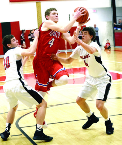 Seth Staskey TO THE HOLE — Toronto's Nate Karaffa drives to the basket between Bellaire defenders Chase Yoho (4) and Tyson Camsky during Tuesday's game. The Big Reds won 69-56.