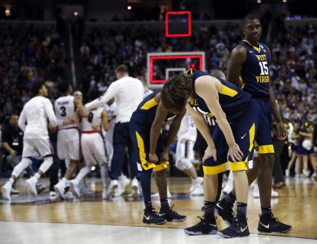 West Virginia players including Nathan Adrian, second from right, and Lamont West (15) stand on the court as Gonzaga celebrates the win during an NCAA Tournament college basketball regional semifinal game Thursday, March 23, 2017, in San Jose, Calif. (AP Photo/Tony Avelar)