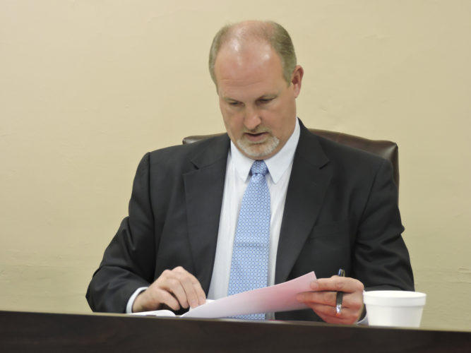 Harrison County Commissioner Paul Coffland read from the meeting agenda Wednesday. Commissioners approved bids for a new county records facility, as well as granting approval to the engineer's office to advertise for bids to paint center lines. — Dylan McKenzie