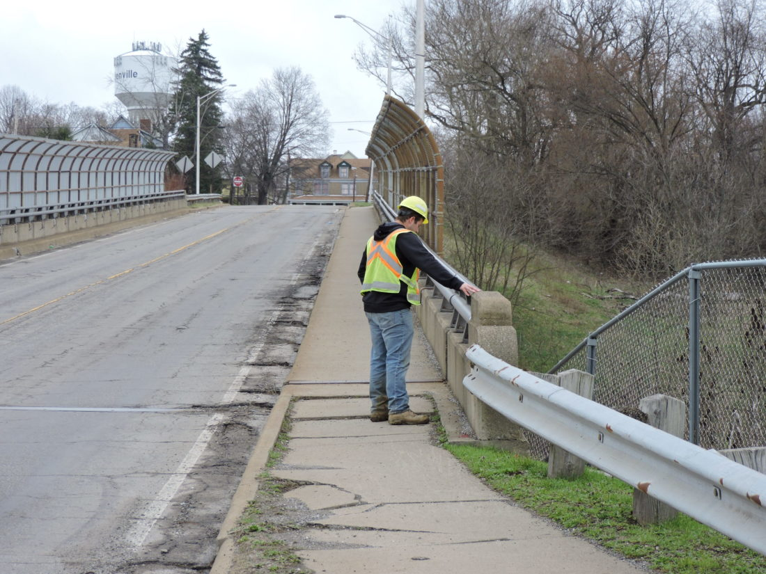 READYFOR CONSTRUCTION — Ohio Department of Transportation Project Engineer Zach Evick examined the sidewalk and parapet on the Lawson Avenue Bridge Wednesday. The bridge will close to all traffic at 6:30 a.m. Monday for 90 days so the concrete base, sidewalk and guardrail can be replaced. - Dave Gossett