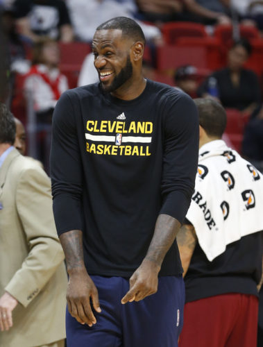 Cleveland Cavaliers forward LeBron James stands during a time out in the first half of an NBA basketball game between the Miami Heat and the Cleveland Cavaliers, Monday, April 10, 2017, in Miami. James and Kyrie Irving were both held out of Cleveland's game at the Miami Heat. James was listed as having a right calf strain, and Irving has soreness in his surgically repaired left knee. (AP Photo/Wilfredo Lee)