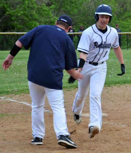 GOING LONG — Buckeye Local's Owen Long rounds third base and gets a low-five from head coach Anthony Barsch after hitting a three-run home run during a six-run seventh inning in Monday's 12-8 win at Bellaire. (Kim North)
