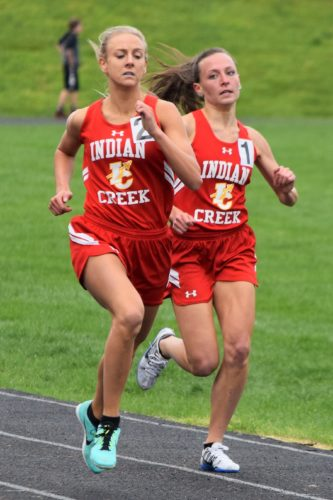 Seth Staskey TEAMMATES UNTIL THE FINISH — IndianCreek's Madison Smith, left, and Kelsey Lewis head to the finish of the 1600 at Bellaire's Nelson Field during Tuesday's Buckeye 8 track and field championship. Smith won.