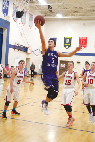 Niagara's Ethan Blagec, center, rises for a layup against Goodman-Pembine on Thursday in Pembine, Wis. The Patriots' Noah Suther (5), Alex Bolssen (25) and Evan Metras (10) look on. (Adam Niemi/The Daily News)