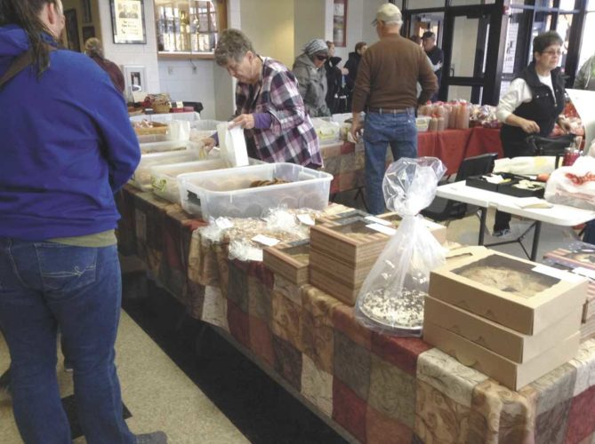 VENDORS ARE BACK with fresh produce and other items for sale on Saturday during the winter Farmer's & Artisan's Market in Iron Mountain. The market is from 9 a.m. to noon at the Izzo-Mariucci Center in Iron Mountain and is held once a month during the months of November to April. Shown here are some visitors at a recent market looking over the goods for sale.