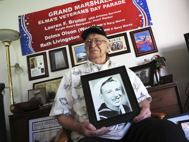 LAUREN BRUNER, ONE of five remaining survivors of the USS Arizona that was attacked in Pearl Harbor on Dec. 7, 1941, holds a 1940 photo of himself, at his home in La Mirada, Calif. (AP Photo/Reed Saxon)
