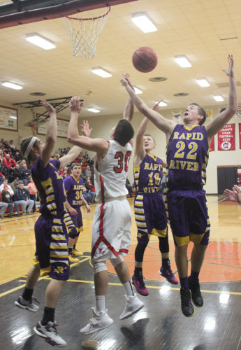 Logan Hardwick of Rapid River reaches for a rebound Thursday in Powers against North Central's Jason Whitens (30). (Dennis Grall/The Daily Press Photo)
