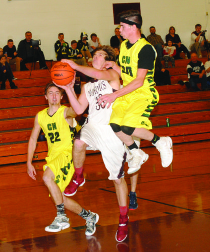 North Dickinson's Jacob Roell (30) drives past Carney-Nadeau's Zach Schettler (22) and Hunter Eichhorn on Thursday in Felch. (Burt Angeli/The Daily News)