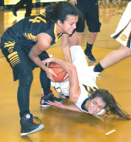 Iron Mountain's Brianna Hoffman, right, battles Gwinn's Kia Evans, left, on Friday. The Mountaineers won on a last-second shot. (Theresa Proudfit/The Daily News)