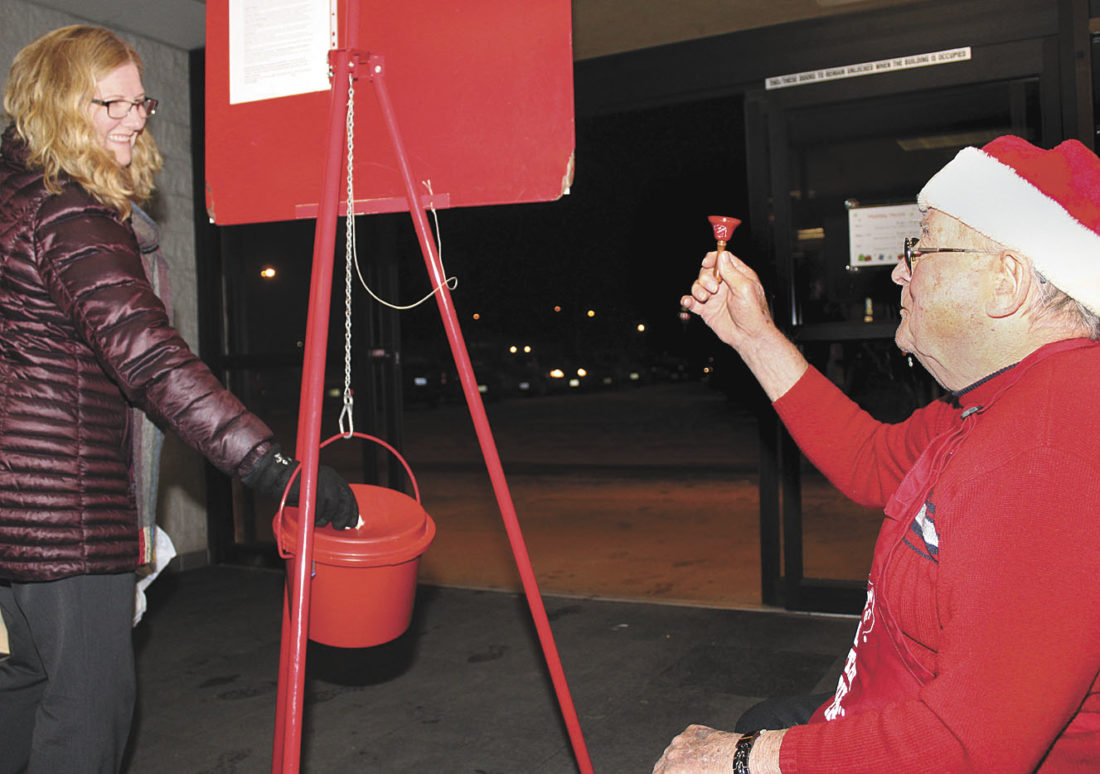Theresa Proudfit/Daily News Photo Karen Shields of Kingsford makes a donation to the Salvation Army as Walter Jensen rings the bell at Shopko in Kingsford. The bell-ringing campaign, which kicked off Nov. 11, is in need of volunteers for two-hour shifts.