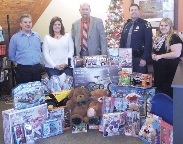 ames Quayle, financial associate of Thrivent Financial, partnered with Michigan State Police Trooper Geno Basanese to host a Toys for Tots drive during Iron River's Christmas in Lights Parade on Dec. 3. The West Iron County Key Club members walked along the parade route and collected not only a multitude of toys from spectators but also a total of $280 in cash to help make this toy drive a great success. Shown here, from left, with some of the items collected are Stephen Stutz, Jenny Marcell, Jim Quayle, Geno Basanese and Erika Lindwall.