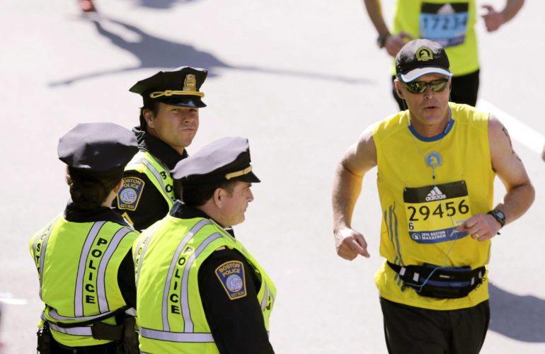 "In this April 18 file photo, actor Mark Wahlberg, center left, dressed as a Boston Police officer, watches runners cross the finish line as he films a scene for the ""Patriot's Day"" movie at the 120th Boston Marathon in Boston. Wahlberg's movie about the bombings during the 2013 Boston Marathon will be released nationwide Jan. 13. (AP file photo)"