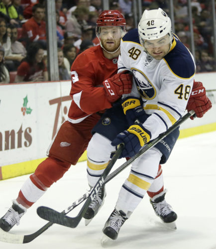 Buffalo left wing William Carrier (48) is knocked off the puck by Detroit Red Wings defenseman Nick Jensen (3) on Tuesday in Detroit. (Duane Burleson/AP Photo)