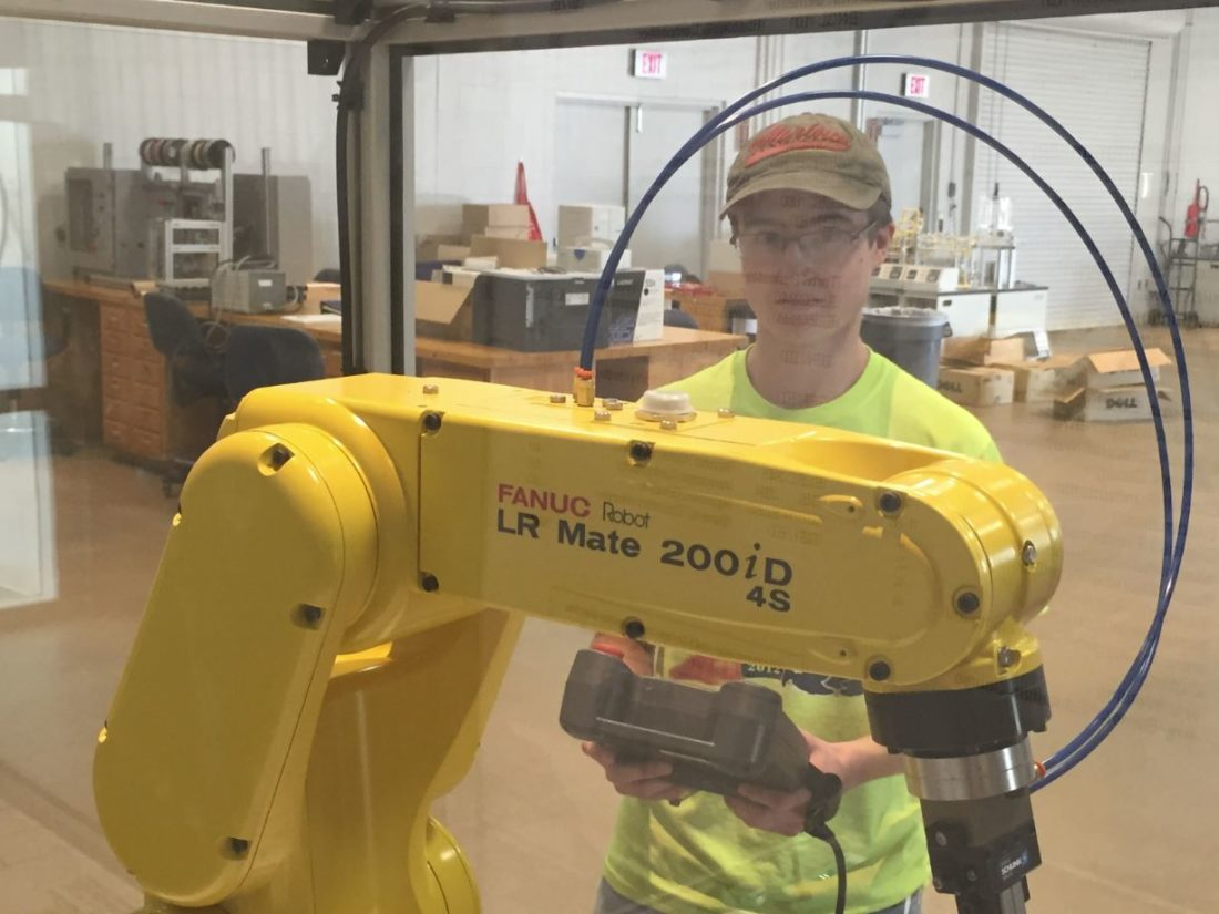 In a file photo, Bay College mechatronics student Andrew Vandermissen works with a Fanuc robot. An agreement between Bay College and Michigan Tech is part of a project aimed at revamping robotics education.