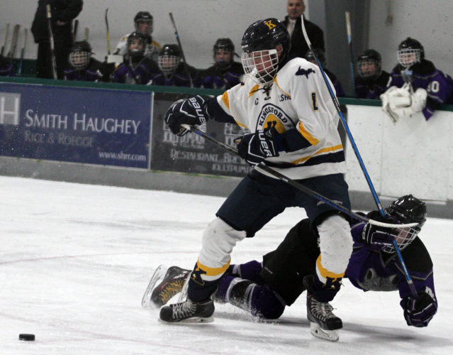 Kingsford's Daunte Fortner, left, battles for the puck against Bay City's Cy Freysinger during the North/South Showcase tournament on Friday in Traverse City. Bay City won 2-1. (James Cook/Traverse City Record-Eagle)