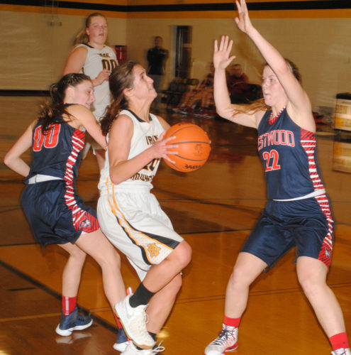 Iron Mountain's Brianna Hoffman (20) drives past Westwood's Lauren Farley (00) and Elizabeth Farley (22) in Monday's Mid-Peninsula Conference game. (Burt Angeli/The Daily News)