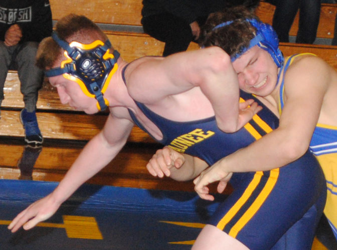 Kingsford's Jonathan Schmutzler grabs Negaunee's Zack Champion in their 152-pound match Wednesday. Schmutzler had one of the Flivvers' four pins in a 42-18 victory. (Burt Angeli/The Daily News)